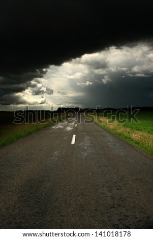 Asphalt road and dark storm clouds over it - stock photo