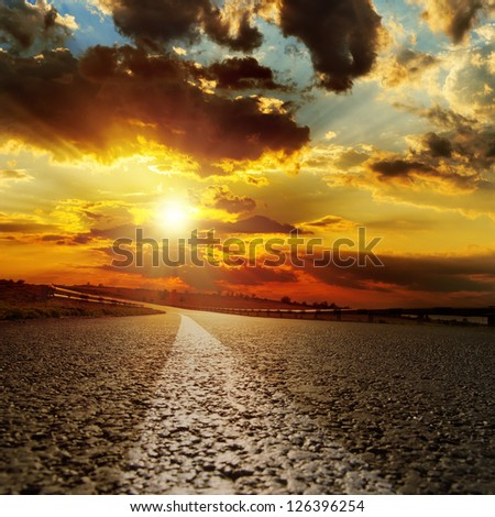 asphalt road and dramatic sunset over it - stock photo