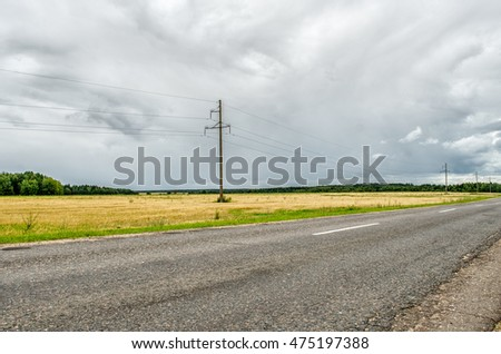 asphalt road and forest. Summer landscape with country road and field of wheat. Road lane and deep sky. Nature design. asphalt road and perfect green field.