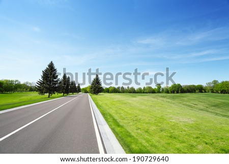 Asphalt road and grassy green field. Summer landscape with blue sky - stock photo