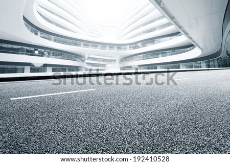Asphalt road and modern office building - stock photo