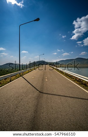 Asphalt road and street lamp with lake and mountain in the park