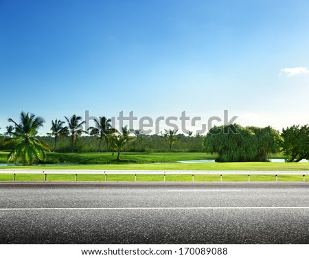 asphalt road and tropical forest - stock photo
