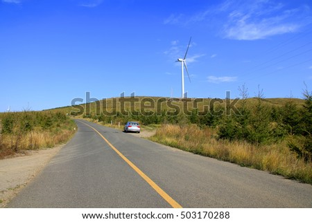 Asphalt road and wind turbines
