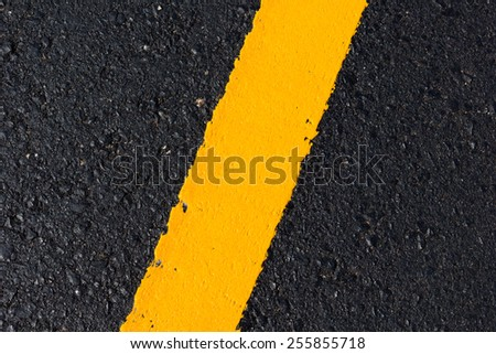 Asphalt road as abstract background, yellow line on the road texture. - stock photo