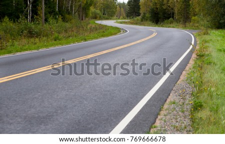 Asphalt road. Autumn day. Curves ahead. Yellow line. Dangerous to drive. Slippery highway.