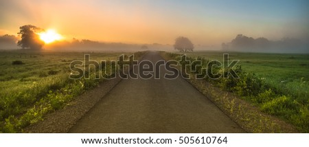asphalt road between green fields while a foggy sunrise