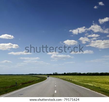 Asphalt road between the field - stock photo
