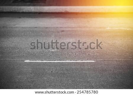 Asphalt road close up. Vintage filter. - stock photo