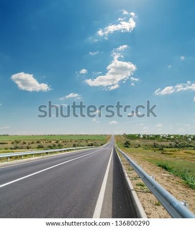 asphalt road closeup under cloudy blue sky - stock photo