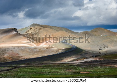 Asphalt road from Myvatn lake to Hverarond area among mud hills and lava fileds on a cloudy day, North Iceland - stock photo