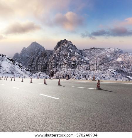 asphalt road front of snow scene of huangshan hill - stock photo