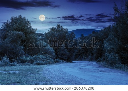 asphalt road going in mountains and passes through the green forest in shade of clouds at night in full moon light - stock photo