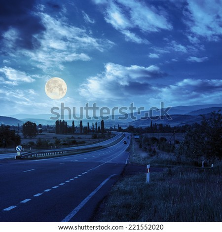 asphalt road going off into the distance on the left, passes through the green shaded forest and village in mountains at night in full moon light - stock photo