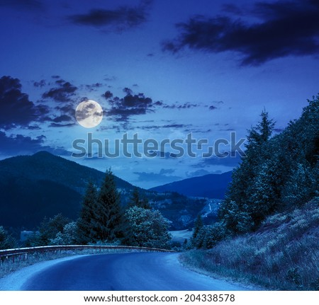 asphalt road going off into the distance on the left, passes through the green shaded forest at night in moon light - stock photo
