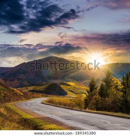 asphalt road going off into the mountain passes through the green shaded forest near rural places at sunset - stock photo