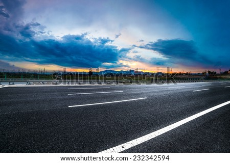 Asphalt road High way Empty curved road clouds and sky at sunset - stock photo