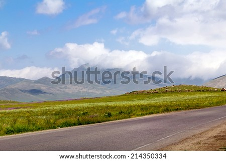 Asphalt road in a mountain valley - stock photo