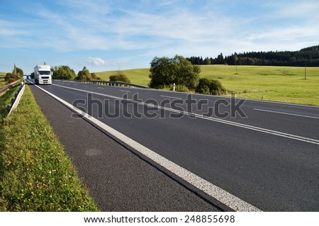 Asphalt road in a rural landscape. The arriving white truck on the road. Meadow and forest in the background. - stock photo