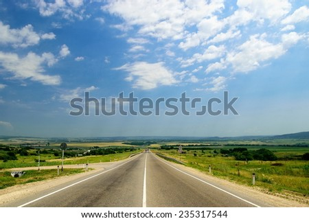 Asphalt road in a summer field - stock photo
