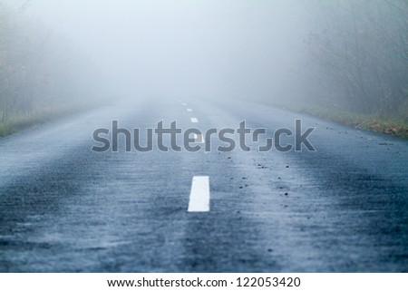 Asphalt road in an autumn fog - stock photo