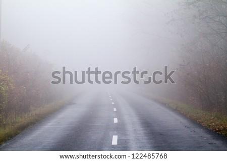 Asphalt road in an autumn fog - stock photo
