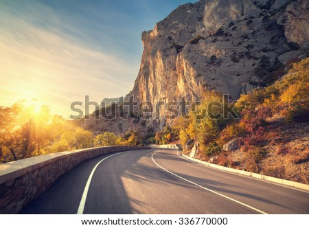 Asphalt road in autumn forest at sunrise. Crimean mountains. - stock photo