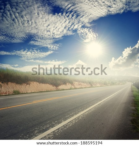 Asphalt road in forrest and sun sky - stock photo