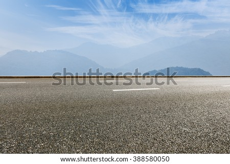 asphalt road in front of the fuzzy mountain - stock photo