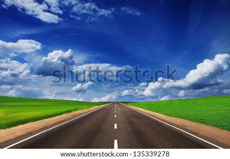 Asphalt road in green fields under beautiful sky - stock photo