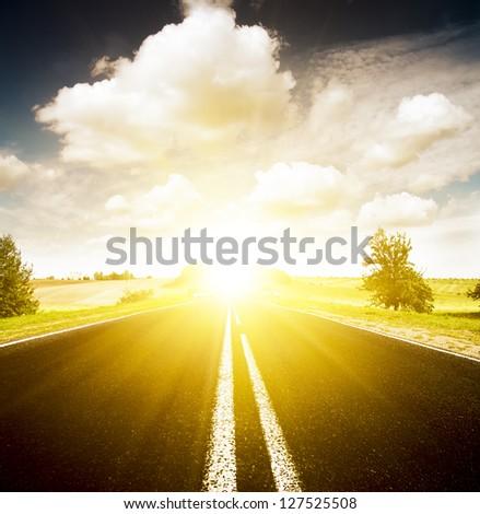 Asphalt road in green meadow. Belarus.  Sunset - stock photo