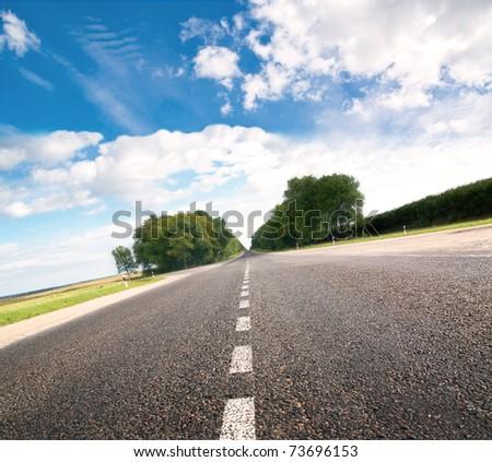Asphalt road in green sunset meadow - stock photo