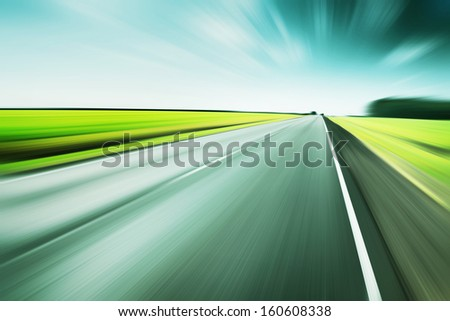 Asphalt road in motion blur at moody day. - stock photo