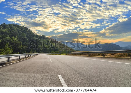 asphalt road in mountain hill with sunset background - stock photo