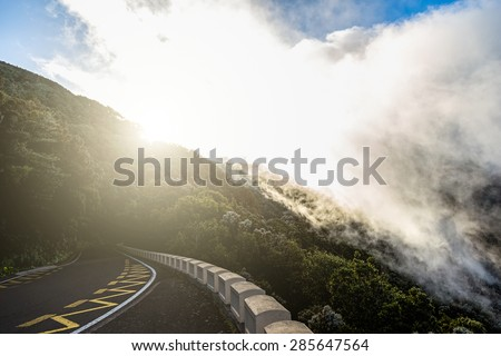 Asphalt road in mountains or rocks and sky with sun and sunlight and clouds over peak in Tenerife Canary island, Spain at sunset
