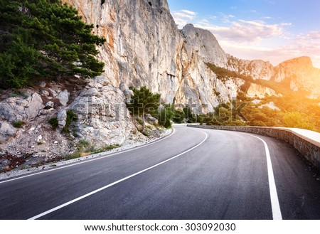 Asphalt road in summer forest at sunset. Crimean mountains  - stock photo