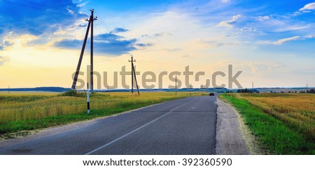 Asphalt road in the countryside. Sunset over the field and the road. Picturesque evening sky with clouds. Panoramic shot.