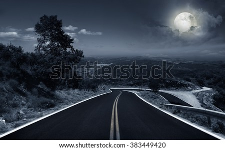 asphalt road in the mountains in the moonlight - stock photo