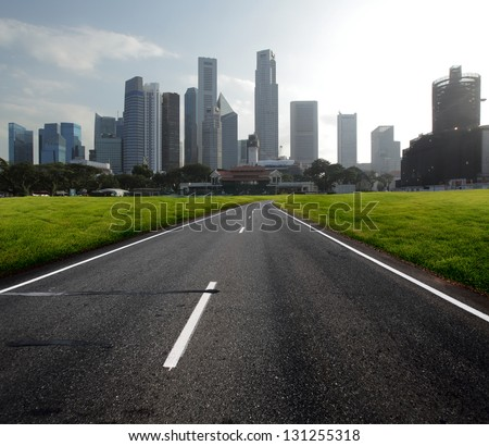 Asphalt road leading to a city with tall buildings through green meadow - stock photo