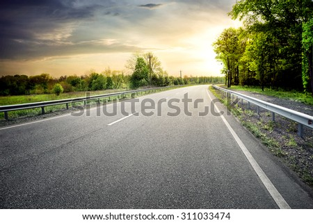 Asphalt road leaving for turn to the sun under a dramatic sky - stock photo