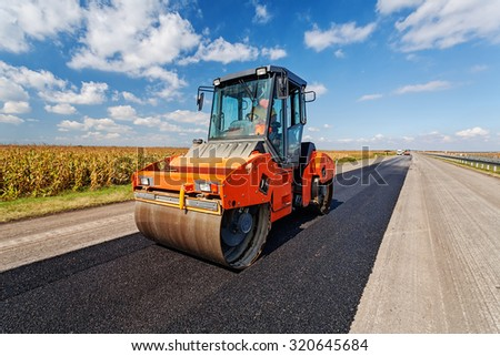 Asphalt road making construction site with heavy machines - stock photo