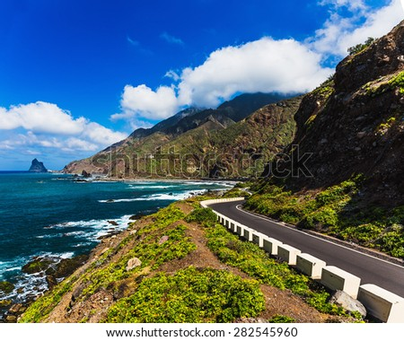 Asphalt road near coast of Atlantic ocean with mountains and blue sky with clouds in Tenerife Canary island, Spain at spring or summer