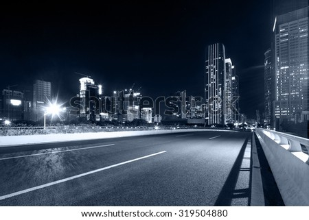 asphalt road near skyscrapers of a modern city at night
