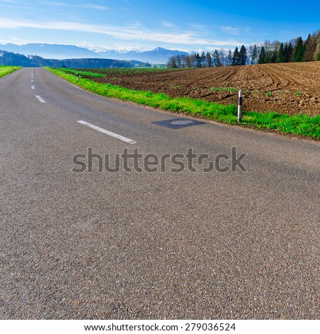 Asphalt Road on the Background of Snow-capped Alps in Switzerland - stock photo