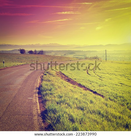 Asphalt Road on the Background of Snow-capped Alps, Sunset in Switzerland, Instagram Effect - stock photo