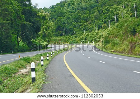Asphalt road sharp curve along with tropical forest zigzag ahead.