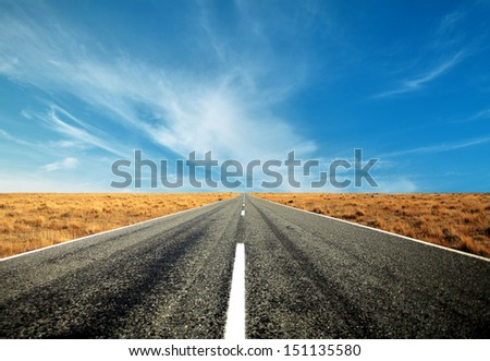 asphalt road straight through the brown field with blue sky and cloud in autumn - stock photo