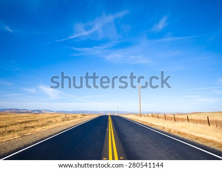 Asphalt road through a golden yellow grass field and clouds in blue sky in summer day - stock photo