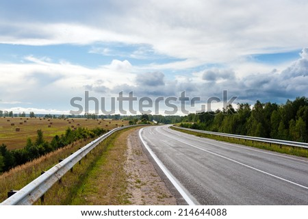 asphalt road through the fields under the clouds in summer day - stock photo