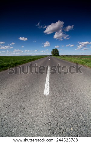 asphalt road through the green field - stock photo